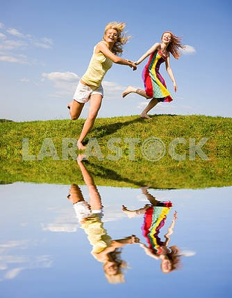 Two happy girls jumping
