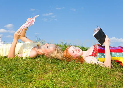 Two beautiful girls with notebook outdoors. Lay on the green gra