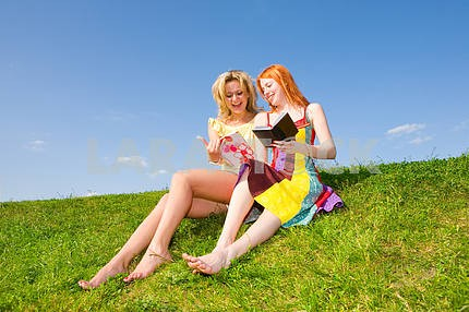 Two beautiful girls with notebook outdoors. Sitting on the green