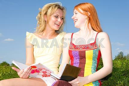 Две красивые девушки с ноутбуками на открытом воздухе
