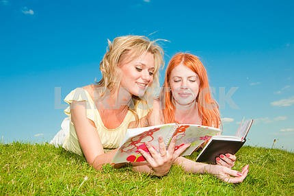 Two beautiful girls with notebooks outdoors. Lay on the green gr