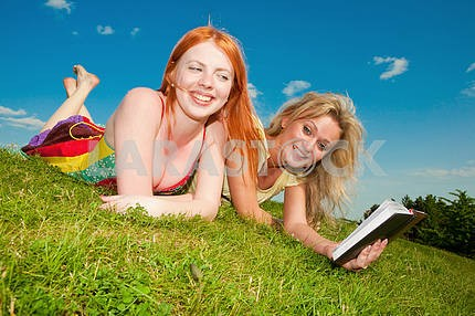 Две красивые девушки с ноутбуками на открытом воздухе . Положите на зеленой гр