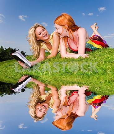 Две красивые девушки с ноутбуком на открытом воздухе . Положите на зеленом гра