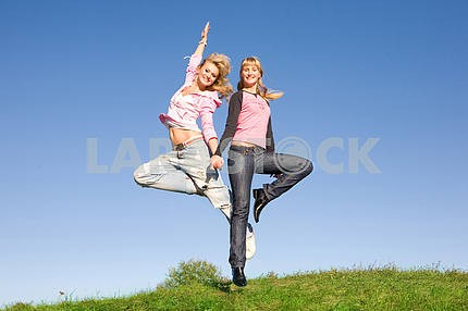 Two happy girls jumping on green meadow.