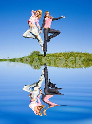 Two happy girls jumping on green meadow. Reflected in the water
