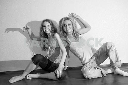 Two attractive young girls sitting close on hardwood floor