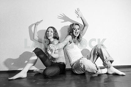 Two attractive young girls sitting close on hardwood floor in ho