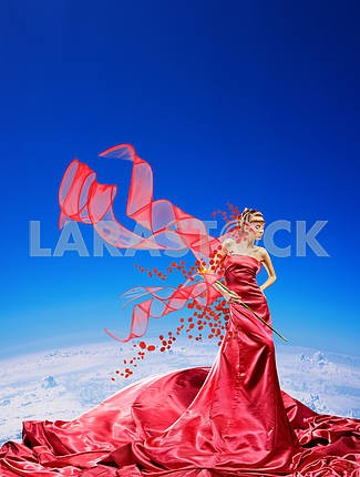 Fabulous girl in a red dress against a blue sky