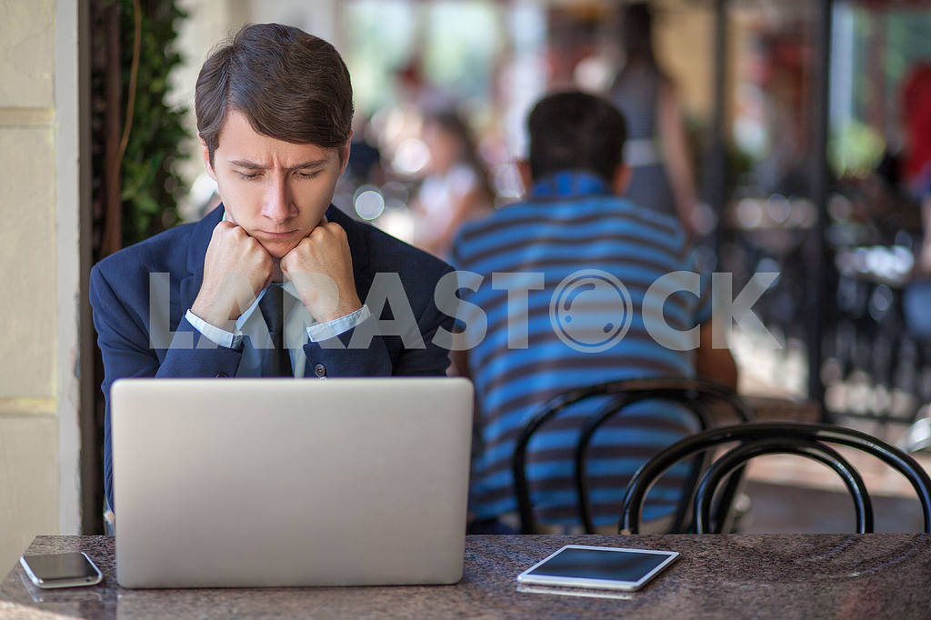 One relaxed young handsome professional businessman working with his laptop, phone and tablet in a noisy cafe. speak with phone. — Image 9534