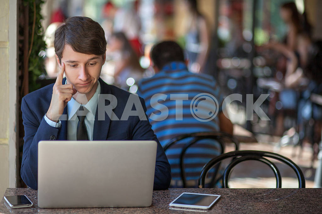 One relaxed young handsome professional businessman working with his laptop, phone and tablet in a noisy cafe. speak with phone. — Image 9535