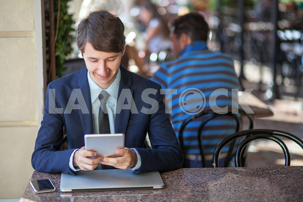 One relaxed young handsome professional businessman working with his laptop, phone and tablet in a noisy cafe. speak with phone. — Image 9537