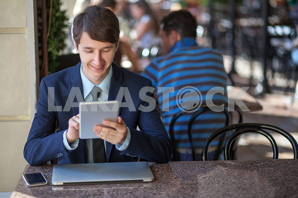 One relaxed young handsome professional businessman working with his laptop, phone and tablet in a noisy cafe. speak with phone. — Image 9538