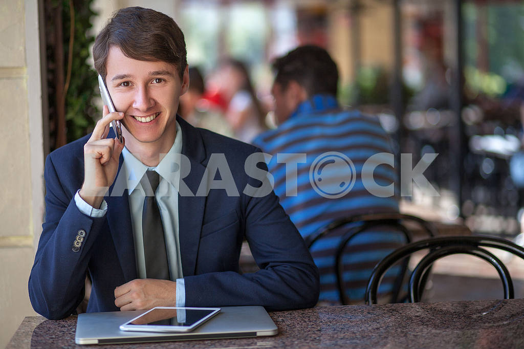 One relaxed young handsome professional businessman working with his laptop, phone and tablet in a noisy cafe. speak with phone. — Image 9544