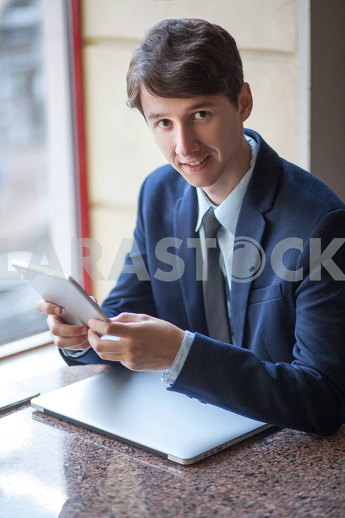 One relaxed young handsome professional businessman working with his laptop, phone and tablet in a noisy cafe. speak with phone. — Image 9545