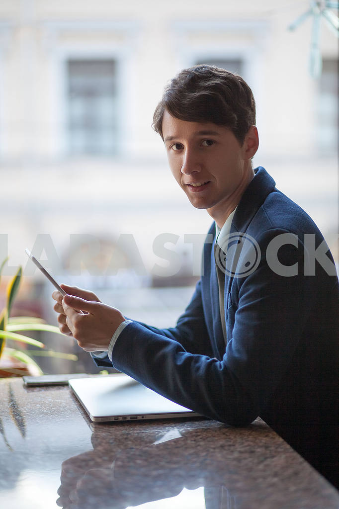 One relaxed young handsome professional businessman working with his laptop, phone and tablet in a noisy cafe. speak with phone. — Image 9546