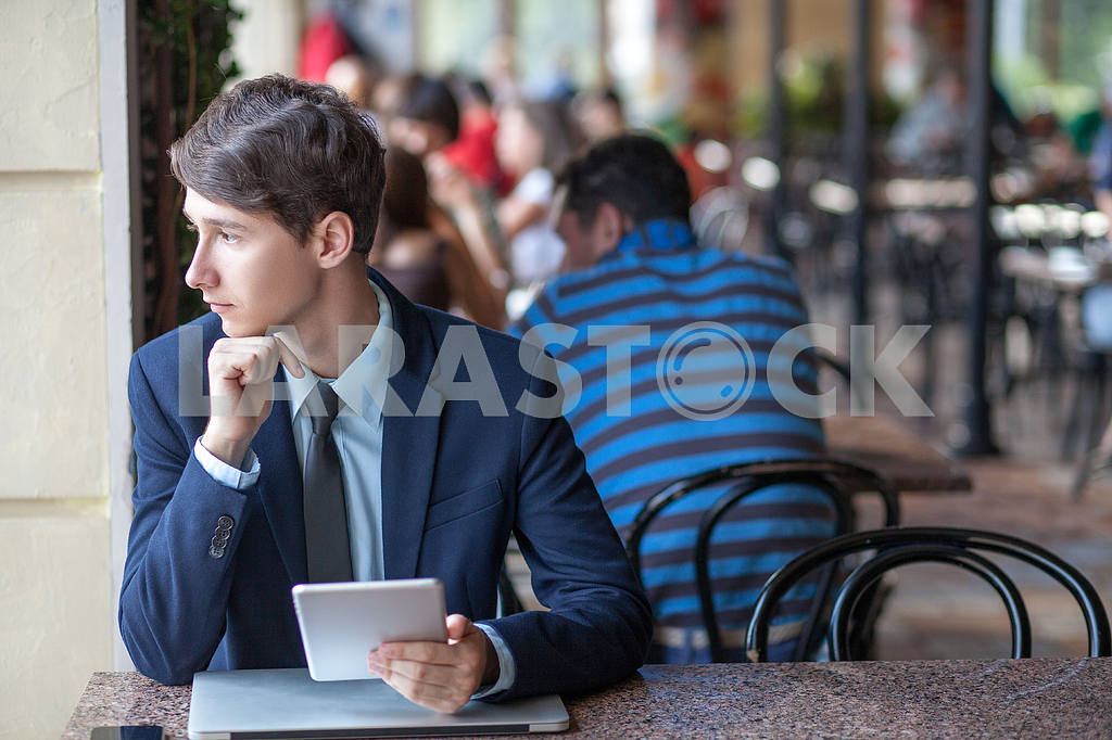 One relaxed young handsome professional businessman working with his laptop, phone and tablet in a noisy cafe. speak with phone. — Image 9547