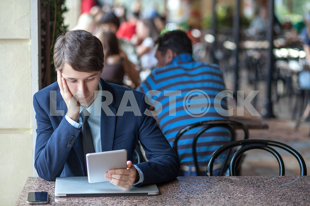 One relaxed young handsome professional businessman working with his laptop, phone and tablet in a noisy cafe. speak with phone. — Image 9548
