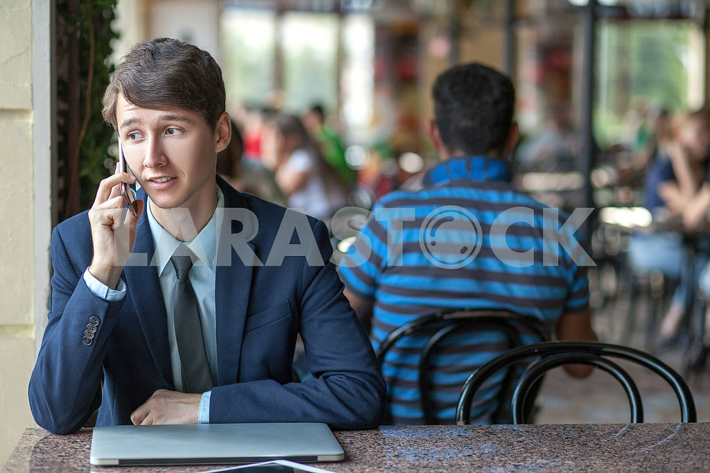 One relaxed young handsome professional businessman working with his laptop, phone and tablet in a noisy cafe. speak with phone. — Image 9549