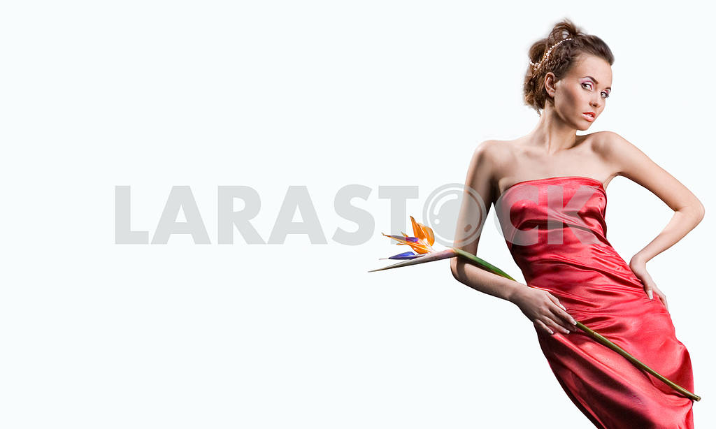 Beautiful girl in a long red dress holds an exotic flower in a h — Image 9626