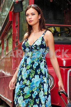 Девушка с чемоданом на фоне красный автобус