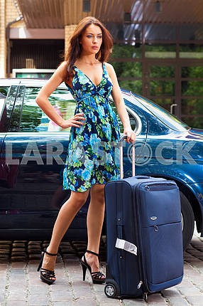 girl with a suitcase on a background of machinery