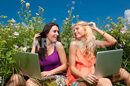 Two beautiful girl with laptop computer in outdoors on green gra