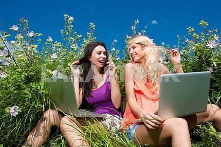 Две красивые девушки на портативный компьютер на открытом воздухе. Сядьте на зеленом гра