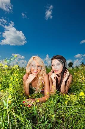 two girlfriends having fun in field of flowers